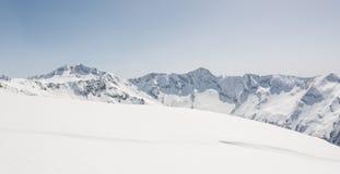 Schnee umfasste Steigung mit Gebirgsrücken in der Rückseite Stockfotografie