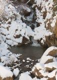 Schnee und Eis bedeckt teilweise einen kleinen Wasserfall Lizenzfreie Stockfotografie