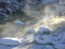Schnee und Sun auf gefrorenem felsiger Gebirgsfluß Lizenzfreies Stockbild