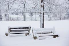 Schnee zwei bedeckte Bänke durch den Fluss Stockbild