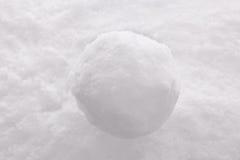 Schneeball auf Schneehintergrund. Lizenzfreies Stockfoto