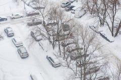 Schneebedeckte Autos parkten im Hof eines Wohngebiets Lizenzfreies Stockfoto