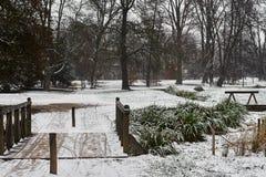 Schneebedeckte Bäume, Büsche und Brücke über kleinem Strom im Stadtpark morgens lizenzfreie stockfotos