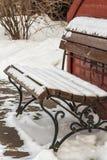 Schneebedeckte Bank im Wintergarten Stockfotografie