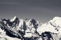 Schneebedeckte Berge des Schwarzweiss-Winters am kalten Sonnentag Lizenzfreie Stockbilder