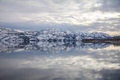Schneebedeckte Berge reflektieren sich symmetrisch im Okanagan See, West-Kelowna stockfotos