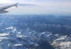 Schneebedeckte Bergspitzen mit Höhenflugzeugen Lizenzfreie Stockfotos