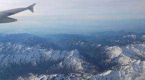 Schneebedeckte Bergspitzen mit Höhenflugzeugen Stockfotografie