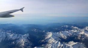 Schneebedeckte Bergspitzen mit Höhenflugzeugen Stockfotos