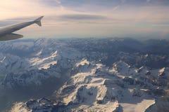Schneebedeckte Bergspitzen mit Höhenflugzeugen Stockbilder