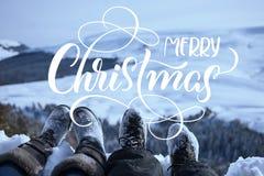 Schneebedeckte Füße von zwei Wanderern auf einem Winter gestalten mit Text frohen Weihnachten landschaftlich Kalligraphiebeschrif stockfotografie