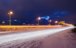 Schneebedeckte Landstraße des Winters nachts glänzte mit Lampen Stockfotografie
