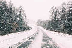 Schneebedeckte offene Straße während eines Winter-Schneesturmes Nachteiliges Wetter Lizenzfreie Stockfotografie