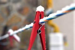 Schneebedeckte rote Wäscheklammer auf der bunten Linie, Nahaufnahme Lizenzfreie Stockfotografie