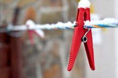 Schneebedeckte rote Wäscheklammer auf der bunten Linie, Nahaufnahme Lizenzfreies Stockfoto