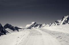 Schneebedeckte Schwarzweiss-Straße mit Spur von Schnee Groomer Stockbilder