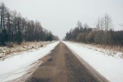 Schneebedeckte Straße des Landes im Winterweinleseeffekt Lizenzfreies Stockbild