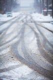 Schneebedeckte Straße, die Kennzeichen der Räder Stockbild