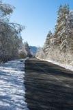 Schneebedeckte Straße des Winters in einem Wald und in einem blauen Himmel Stockbilder