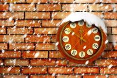 Schneebedeckte Uhr auf Hintergrund der Backsteinmauer Lizenzfreies Stockbild