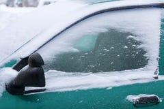 Schneebedeckte Windschutzscheibe und das Seitenfenster des Autos in einem Schneesturm Stockfotos