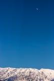 Schneebedeckter Gebirgszug unter einem hohen blauen Himmel und dem Mond Stockfotografie