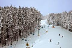 Schneebedeckter Wald des Winters und ein Sessellift für Skifahrer Stockbild