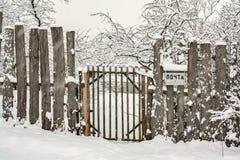 Schneebedeckter Zaun des hölzernen Winters mit Tor und Briefkasten Lizenzfreie Stockbilder