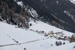 Schneebedecktes Bergdorf am Fuß des Berges am Winternachmittag stockbilder
