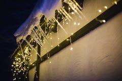 Schneebedecktes Dach eines Hauses verziert mit Girlande lizenzfreie stockfotografie