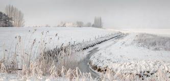 Schneefälle über einem ländlichen Gebiet mit einem schlängelnden Abzugsgraben Lizenzfreie Stockfotos