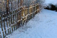 Schneefälle auf hölzernem Palisadenzaun Lizenzfreies Stockfoto