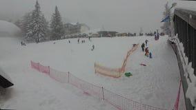 Schneefälle in den Bergen die Kinder gehen den Hügel auf einem Schlitten hinunter stock footage