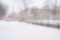 Schneefälle in der Stadt mit unscharfen beweglichen Autos auf Hintergrund Stockfotografie