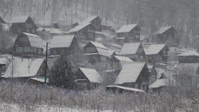 Schneefälle im Dorf, in den kleinen Häuschen und in den Bäumen bedeckt im Schnee stock footage