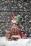 Schneefälle mit Lebkuchenweihnachtsmann-Weihnachtsbirnenschokoladen-Weihnachtsbaum auf Haufen des Schnees gegen hölzernen Hinterg Stockbilder