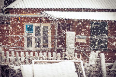 Schneefall-Winter-Wetter im Dorf mit Schneeflocken und altem Hausfenster Lizenzfreie Stockfotos