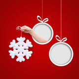Schneeflocke in der Hand auf einem roten Hintergrund Lizenzfreie Stockfotografie
