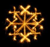 Schneeflocke gemacht durch Wunderkerze auf einem Schwarzen Stockfotos