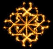 Schneeflocke gemacht durch Wunderkerze auf einem Schwarzen Lizenzfreies Stockfoto