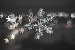 Schneeflocke mit unscharfem Farbhintergrund lizenzfreie stockfotografie