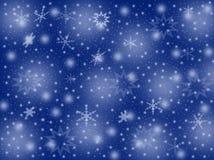 Schneeflocken auf einem blauen Hintergrund Stockbilder