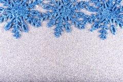 Schneeflocken auf einem Hintergrund von silbernen Pailletten Stockfotografie