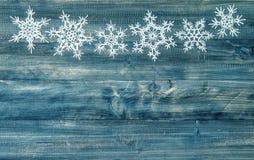 Schneeflocken fassen über rustikalem hölzernem Hintergrund ein Der Junge gelegt auf den Schnee Stockfotografie