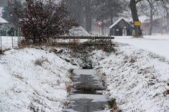 Schneeflocken gefallen auf eine schneebedeckte Landschaft und eine Grabung an einem kalten Wintertag im Bezirk emsland Deutschlan stockbilder