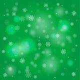 Schneeflocken und undeutliche Lichter auf grünem Hintergrund Lizenzfreies Stockfoto
