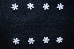 Schneeflockendekoration der weißen Weihnacht auf schwarzem strukturiertem Hintergrund Stockfoto