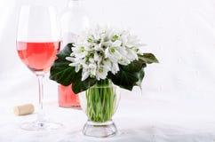 Schneeglöckchenblumenstrauß, weiße Frühlingsblumen und Roséwein auf hellem Hintergrund Kopieren Sie Platz lizenzfreie stockfotos
