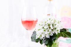 Schneeglöckchenblumenstrauß, weiße Frühlingsblumen und Roséwein auf hellem Hintergrund Kopieren Sie Platz stockfotografie