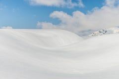 Schneehügel gegen klaren blauen Himmel Stockfotografie